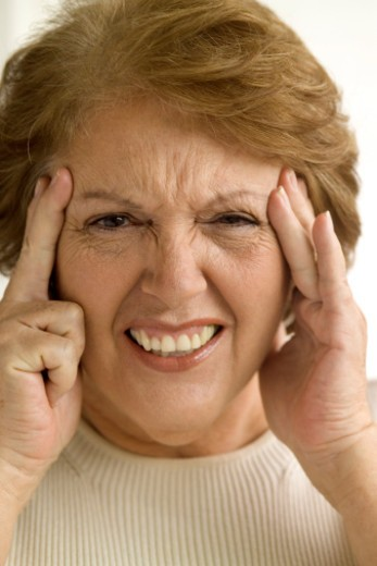 Elderly woman grimacing and holding her head in pain, close-up : Stock Photo