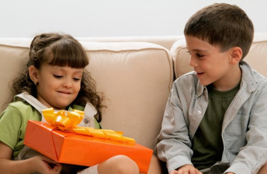 Smiling boy giving girl gift, close-up : Stock Photo