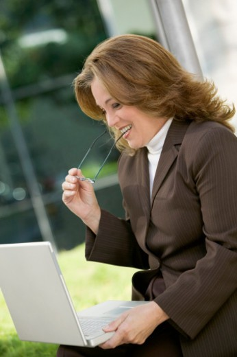Smiling businesswoman biting frame of glasses and working on laptop outdoors , close-up : Stock Photo