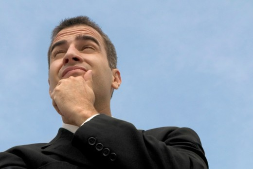 Businessman outdoors with hand on chin, low angle view, close-up : Stock Photo