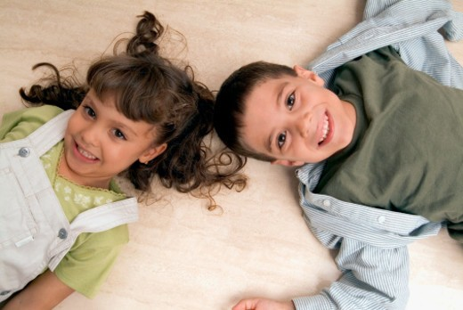 Stock Photo: 1598R-287480 High angle view of a young boy and girl lying on the floor