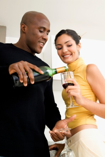 Man pouring red wine into a woman's glass : Stock Photo