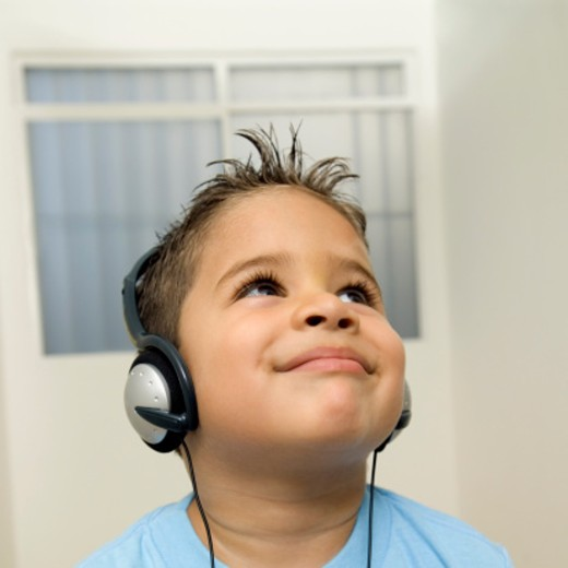 Boy listening to music on headphones and looking up : Stock Photo