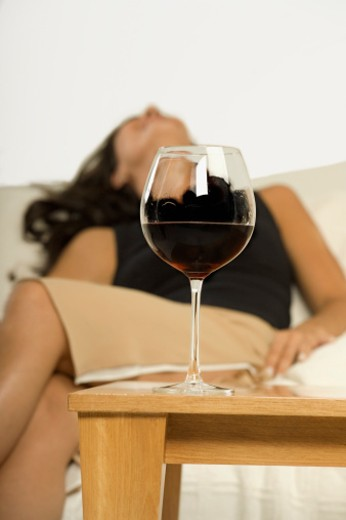 Close-up of a glass of red wine lying in front of a young woman (blurred) : Stock Photo