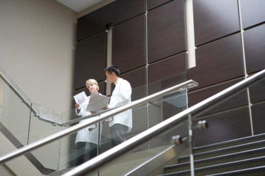 Stock Photo: 1598R-289362 Two people in lab coats talking on stairs