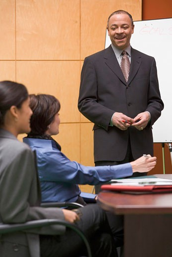 Mature businessman giving presentation to coworkers in boardroom : Stock Photo