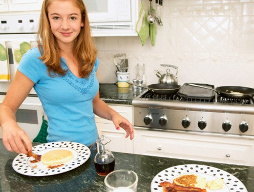 Teenage girl (14-16) making pancakes and bacon, smiling, portrait : Stock Photo