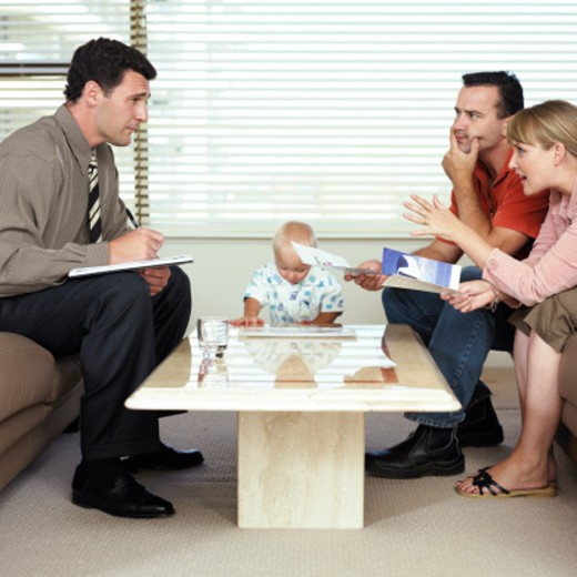 Couple with baby boy (12-15 months) talking to male advisor : Stock Photo