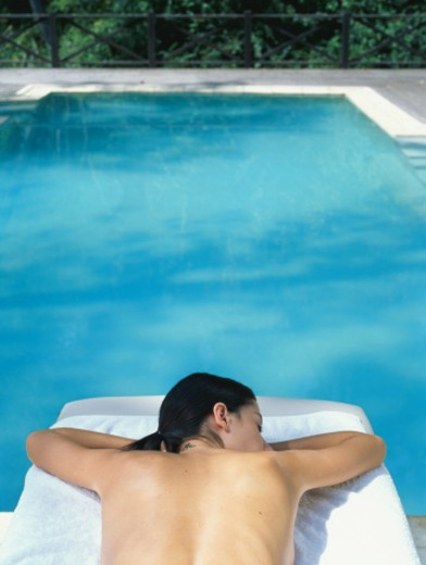 Woman lying on massage bed by swimming pool : Stock Photo