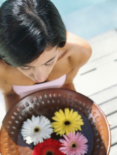 Woman holding bowl containing flowers floating on water, overhead view : Stock Photo