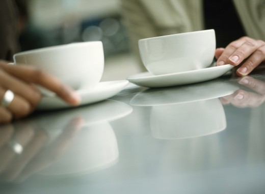 Two young women holding coffee cups, close-up (focus on cups) : Stock Photo
