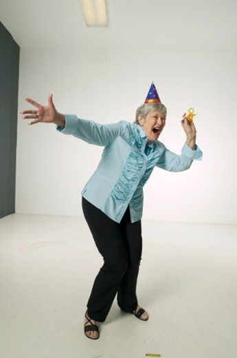 Senior woman wearing party hat, dancing in studio, portrait : Stock Photo