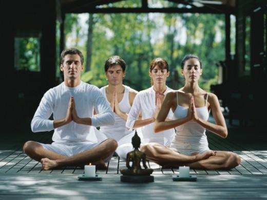 Two men and two women sitting cross-legged, meditating, eyes closed : Stock Photo