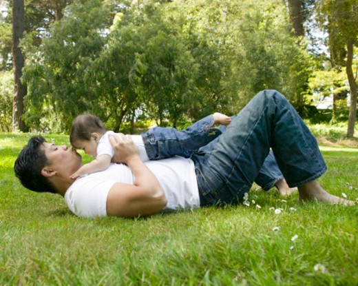 Father lying in grass, holding baby girl (9-12 months), side view : Stock Photo