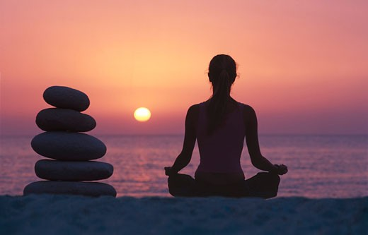 Young woman meditating by pile of stones on beach, sunset, rear view : Stock Photo
