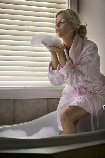 Stock Photo: 1598R-3611 Young woman blowing bath foam in bath tub