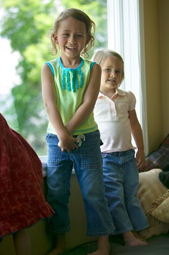 Two sisters (3-4), (4-5), standing on couch in living room, portrait : Stock Photo