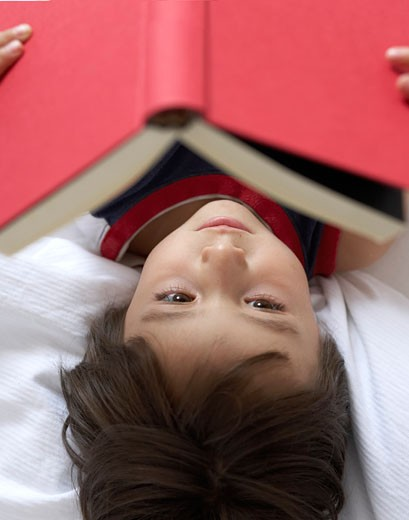 Stock Photo: 1598R-36497 Boy (4-6) reading in bed, elevated view (focus on face)