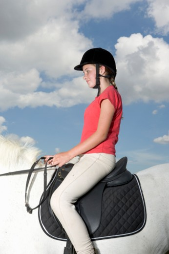 Teenage girl (13-15) riding horse, side view : Stock Photo