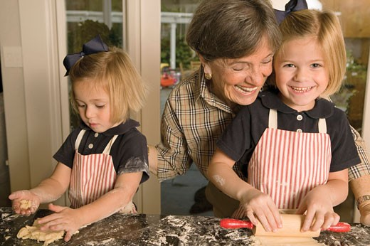 Grandmother in kitchen with two granddaughters (3-5), rolling dough : Stock Photo