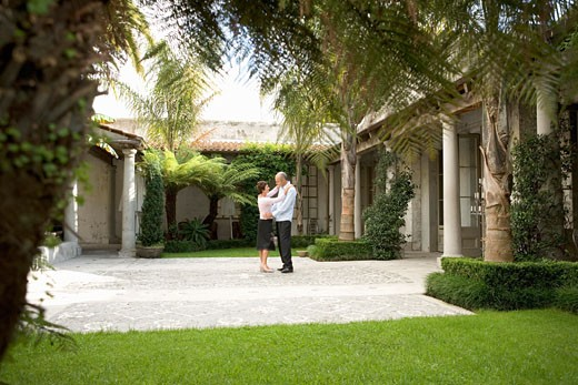 Mature couple dancing in courtyard, side view : Stock Photo