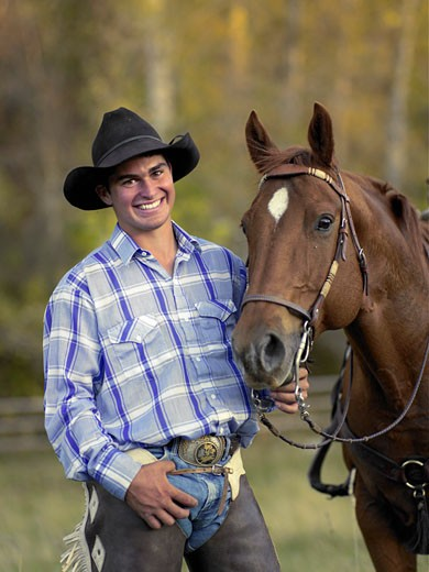 Stock Photo: 1598R-37928 Cowboy standing next to horse, portrait