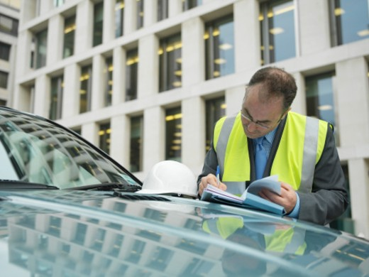 Man leaning on car writing on paperwork : Stock Photo