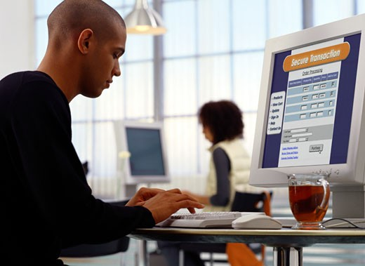 Young man shopping on ecommerce site at internet cafe : Stock Photo