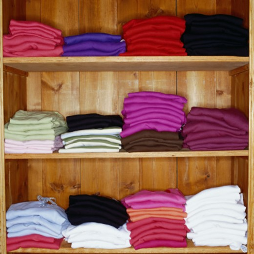 Stock Photo: 1598R-42431 Folded shirts on wooden clothing store shelves, close-up