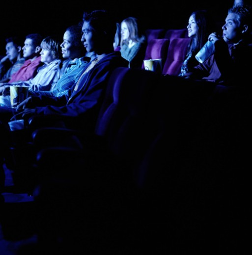 Group of young people watching movie, side view : Stock Photo