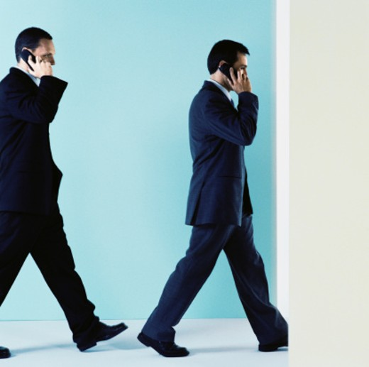 Two businessmen talking on mobile phones : Stock Photo