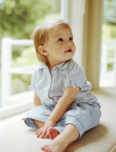 Baby sitting by window : Stock Photo