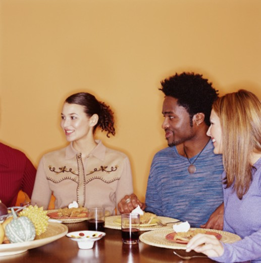 Group of young adults eating dessert and talking at dinner party : Stock Photo