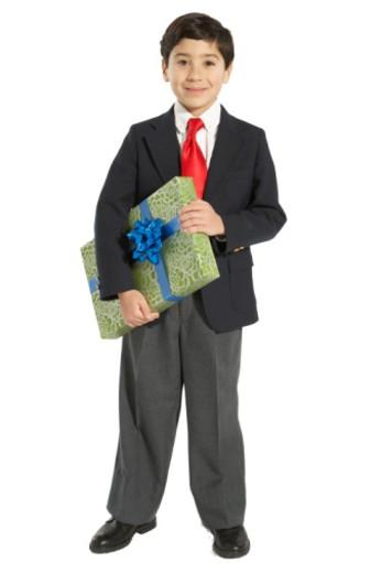 Boy (8-10) holding gift, smiling, portrait : Stock Photo