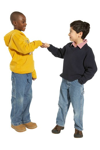 Stock Photo: 1598R-4511 Two boys (8-10) bumping fists, smiling, side view