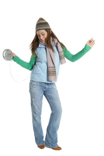 Teenage girl (15-17) wearing headphones, dancing and smiling : Stock Photo