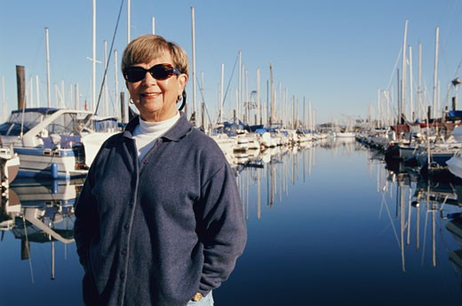 Senior woman wearing sunglasses standing in marina, smiling : Stock Photo