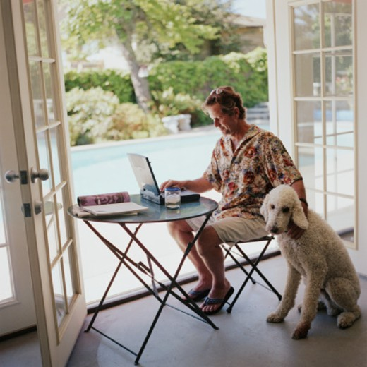 Stock Photo: 1598R-47112 Man working on laptop with poodle by his side