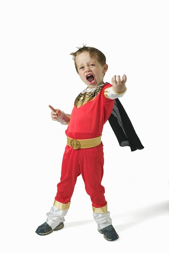 Boy (3-5) wearing superhero costume, thrusting hand out : Stock Photo