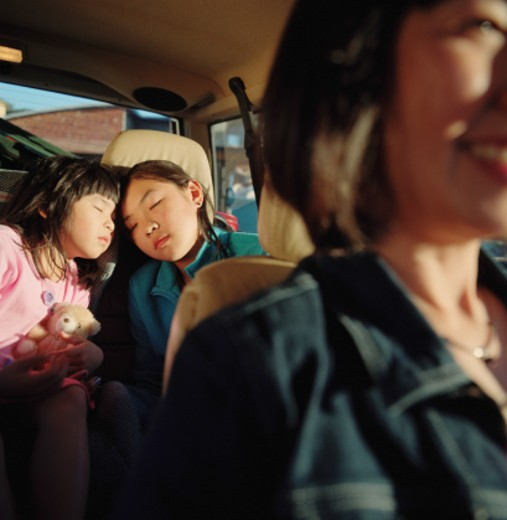 Stock Photo: 1598R-49641 Young girls (5-7) asleep in backseat of car (selective focus)