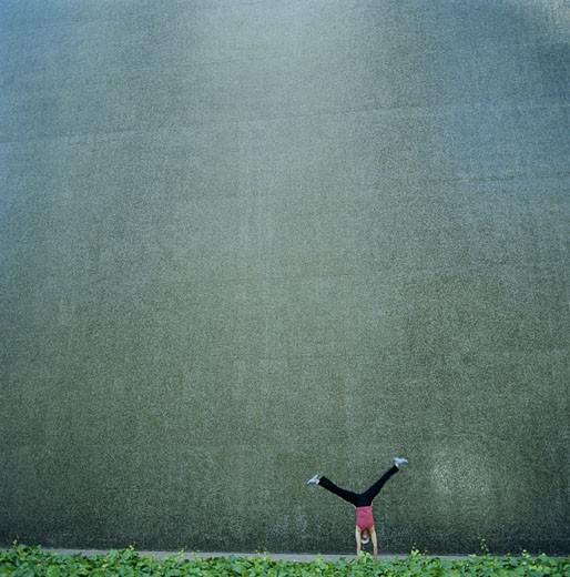 Stock Photo: 1598R-50121 Woman doing cartwheel in front of tile wall