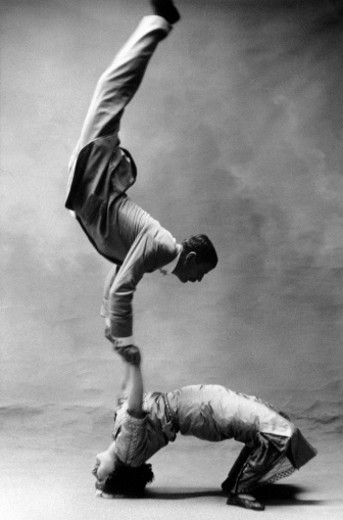 Acrobats performing balancing act, side view (B&W) : Stock Photo