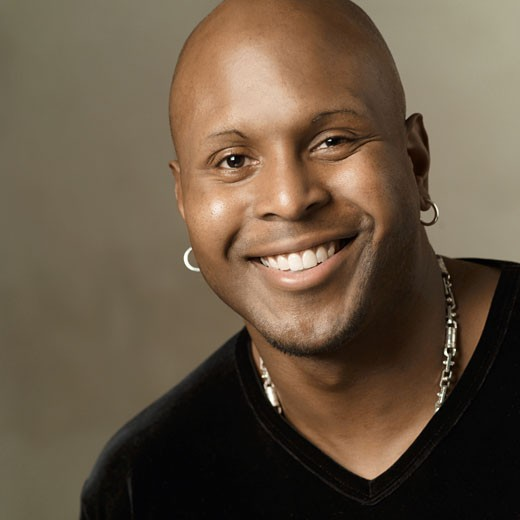 portrait of an african american man in a black shirt as he smiles into the camera : Stock Photo