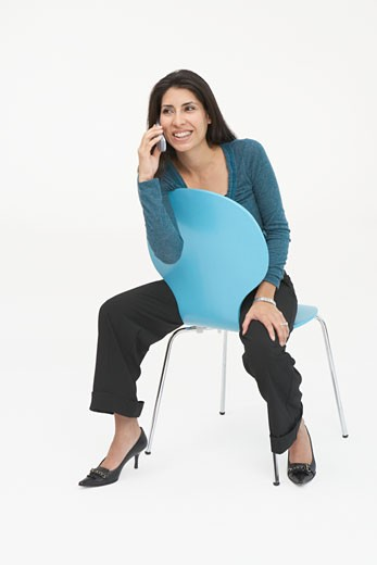 Mid adult woman sitting on a chair and talking on a mobile phone : Stock Photo