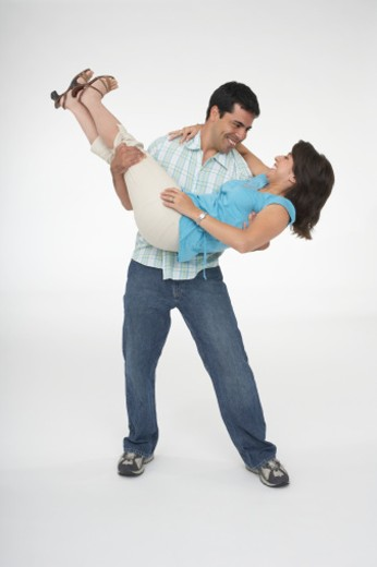 Mid adult man carrying a young woman : Stock Photo
