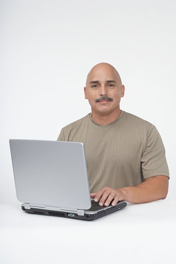 Mature man sitting at a table and working on a laptop : Stock Photo
