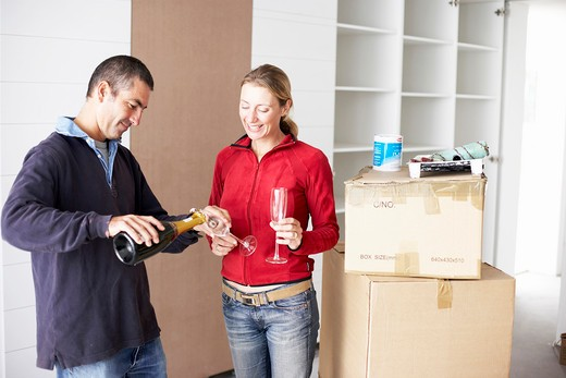 Couple celebrating in new home with champagne, smiling : Stock Photo