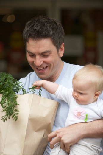 Baby girl is grabbing parsley that is sticking out of the bag. : Stock Photo