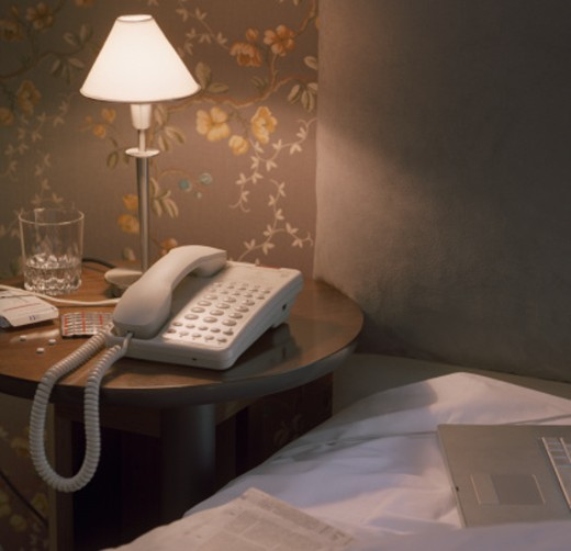 Telephone by tablets on hotel bedside table, laptop and paper on bed : Stock Photo