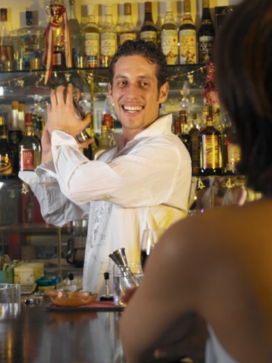 Young male bartender making cocktail for young woman in nightclub : Stock Photo
